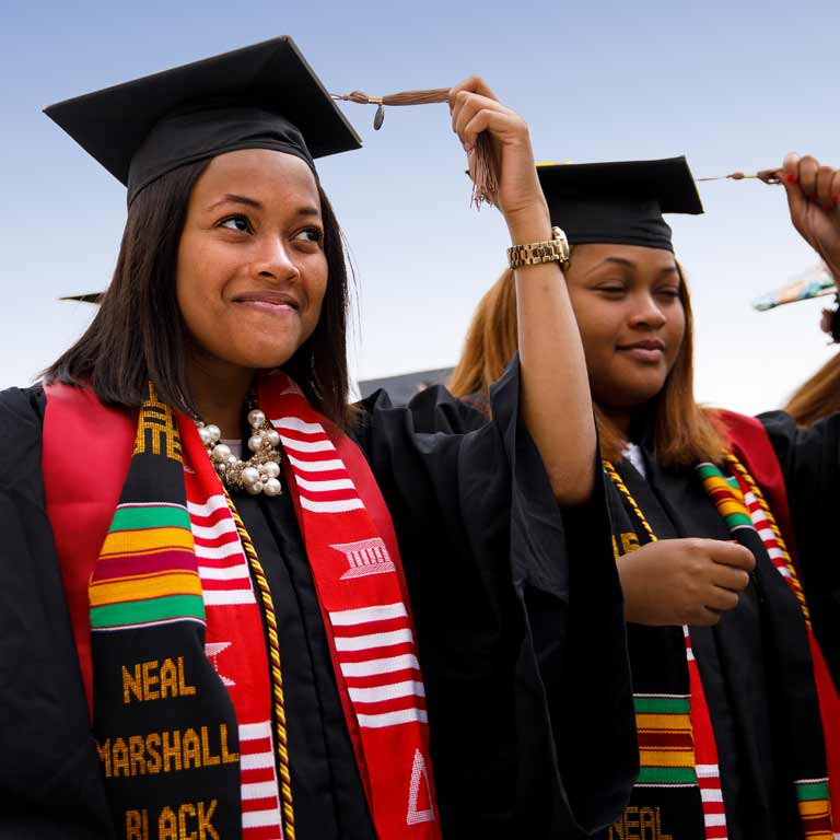 Two IU students wearing Neal Marshall Black Culture Center stoles over their graduation gowns turn the tassels on their mortarboards